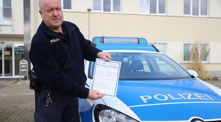 Hauptkommissar Andreas Frommholz von der Polizeiinspektion Fürstenwalde mit einem der Handzettel, die derzeit an viele Haushalte in Storkow (Mark) verteilt werden. Foto: Marcel Gäding
