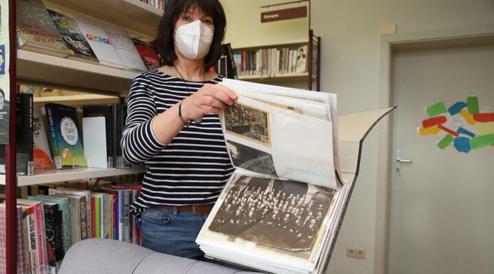 Prall gefüllt ist das Album, das Petra Kather von der Stadtbibliothek Storkow präsentiert. Es enthält historische Postkarten, aber auch Fotos vergangener Zeiten. Foto: Marcel Gäding