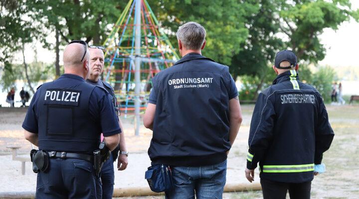 Polizeibeamte, Ordnungsamt und Sicherheitspartner Storkow unterwegs im Park an der Seepromenade in Karlslust. Es soll nicht der letzte Einsatz dieser Art gewesen sein. Foto: Marcel Gäding